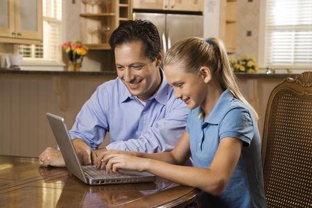 Smiling father and daughter sitting at dining room table working on laptop.  photo