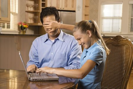 Young girl working on laptop at home covering mans face with hand.  photo