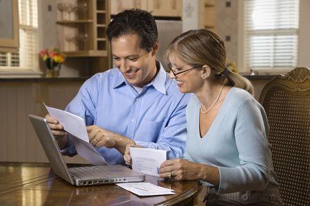 coppia in casa: Paio di pagare le fatture online con un computer portatile a casa. Archivio Fotografico