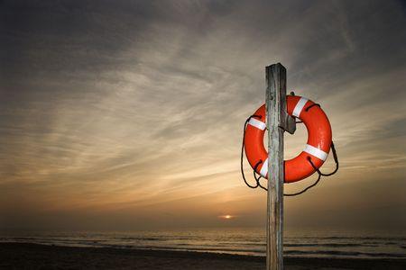 lifesaver: Life Preserver on pole at beach at sunset.  Horizontally framed shot.