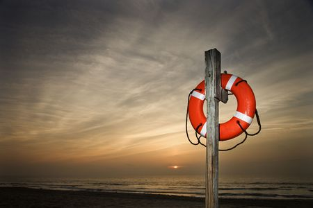 Life Preserver on pole at beach at sunset.  Horizontally framed shot.