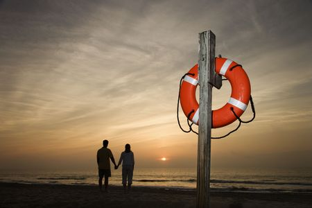 preserver: Silhouette of couple holding hands on beach watching the sunset with life preserver in foreground Stock Photo