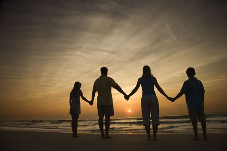 Silhouette of family holding hands on beach watching the sunset. Horizontally framed shot. photo