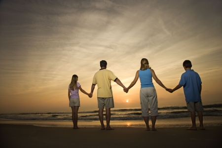 Family of four holding hands on beach watching the sunset. Horizontally framed shot. photo