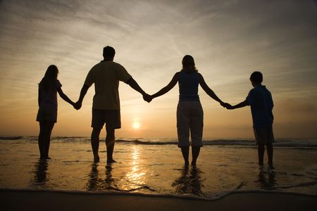 держась за руки: Silhouette of family holding hands on beach watching the sunset. Horizontally framed shot.