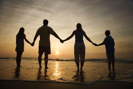 manos sosteniendo: Silueta de explotación familiar las manos en Playa viendo la puesta de sol. Disparo horizontalmente enmarcado.