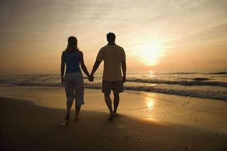 couple holding hands: Silhouette of couple walking on beach at sunset holding hands. Horizontally framed shot.