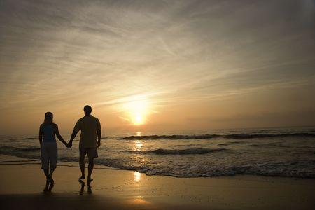 parejas caminando: Silueta de la pareja caminando en la playa al atardecer manos. Disparo horizontalmente enmarcado.