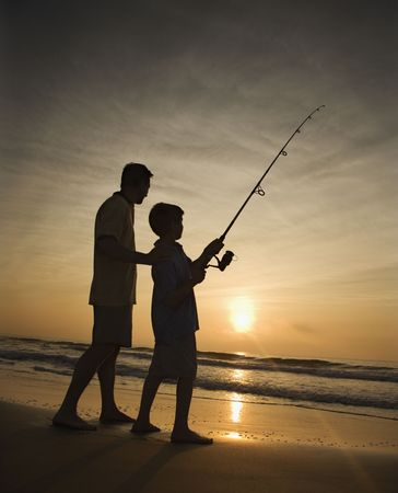 fishing pole: Father and son fishing in ocean surf at sunset.  Vertically framed shot.