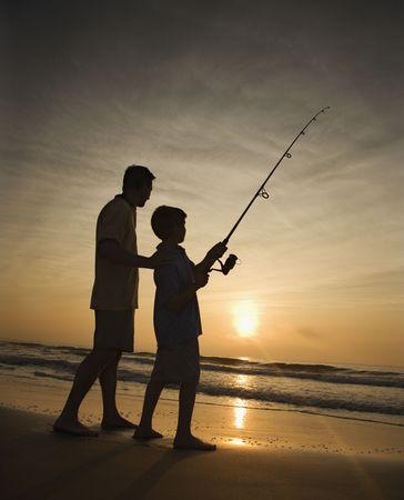 padre e hijo: Padre e hijo de pesca en el oc�ano surf al atardecer. Verticalmente enmarcado disparo.