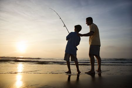 fishing pole: Father and son fishing in ocean surf at sunset.
