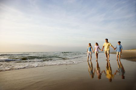 strolling: Family of four holding hands and walking on beach in North Carolina.