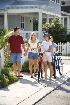 Family of four walking together on sidewalk with bicycles. photo