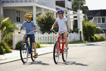 Brother and sister riding bikes together on street.  Horizontally framed shot. photo