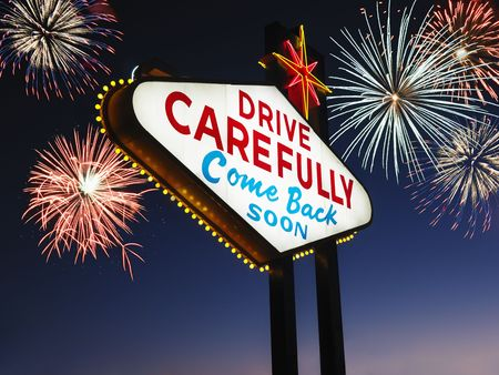 carefully: Las Vegas sign at night reading Drive carefully and Come back soon with fireworks in background. Horizontally framed shot.