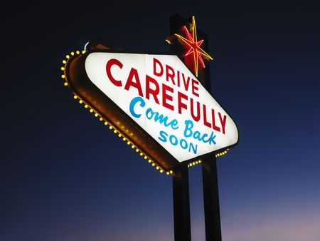 carefully: Las Vegas sign at night reading Drive carefully and Come back soon. Horizontally framed shot. Stock Photo