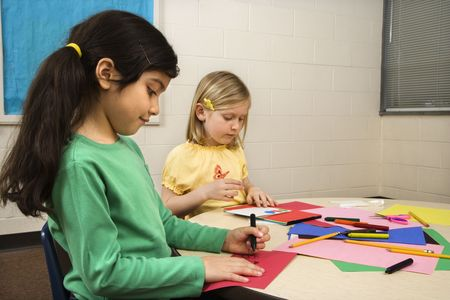 hispanic kids: Two young girls in classroom creating art. Horizontally framed shot. Stock Photo