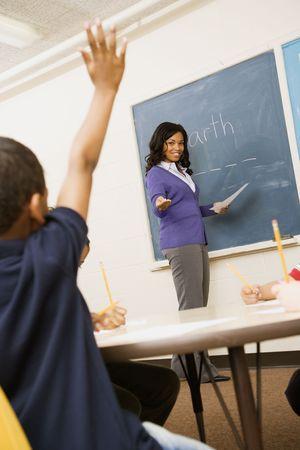 enseignants: Professeur souriante et pointant � �tudiant avec main soulev�e. Vertical abattu.