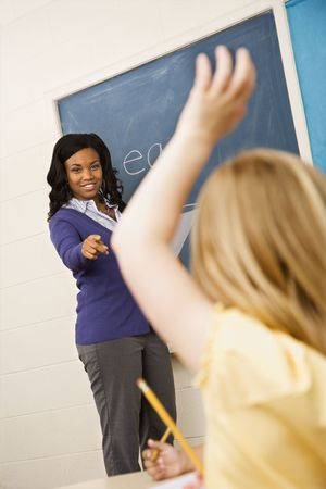 Teacher smiling and pointing to student with hand raised. Vertically framed shot. photo