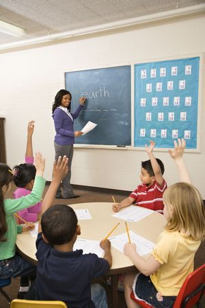 Teacher standing at blackboard with Earth written on it as students sit with hands raised. Stock Photo - 6235464