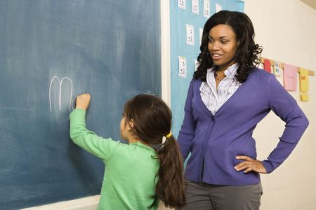 elementary students: Teacher watching young female student write on blackboard. Horizontally framed shot. Stock Photo