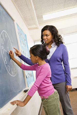 Teacher and female student at the blackboard with clock drawing on it. photo