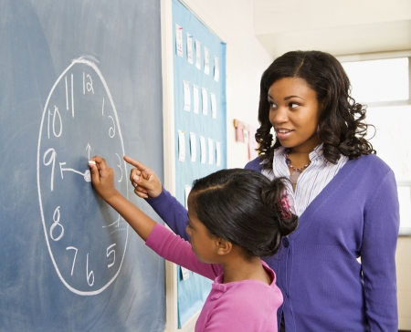 Teacher and female student at the blackboard with clock drawing on it. Stock Photo