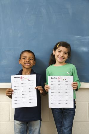 grades: Young students holding spelling tests with good grades. Vertically framed shot.