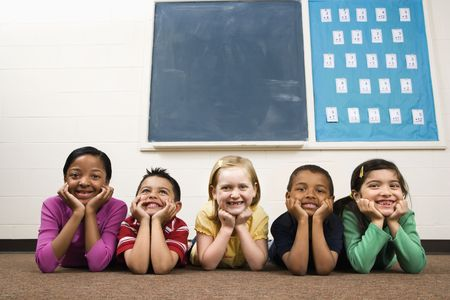 diverse people: Young group of students lying on floor in classroom. Horizontally framed shot. Stock Photo