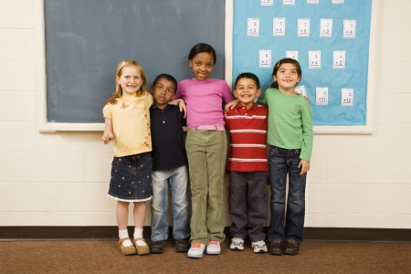 horizontally: Group of diverse young students standing together in classroom. Horizontally framed shot.