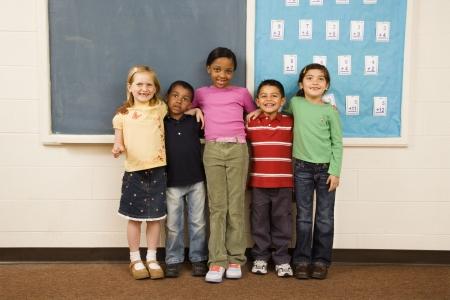 interracial: Gruppe von unterschiedlichen jungen Studenten, die im Klassenzimmer beieinander stehen. Horizontal gerahmten Schuss.