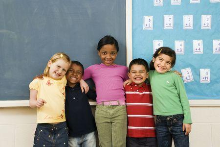 nios hispanos: Grupo de diversos j�venes estudiantes juntos en pie en el aula. Disparo horizontalmente enmarcado. Foto de archivo