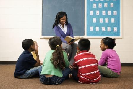 profesores: Libro de lectura de profesor a j�venes estudiantes en el aula. Disparo horizontalmente enmarcado. Foto de archivo