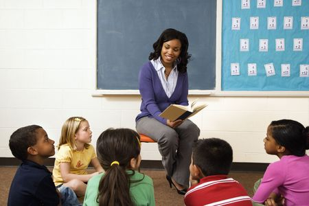 female teacher: Teacher reading book to young students in classroom. Horizontally framed shot.
