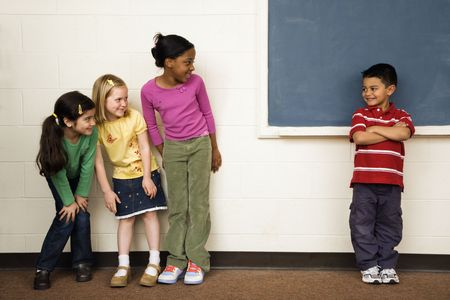 Students standing in classroom. A boy is separate from the girls. Horizontally framed shot. photo