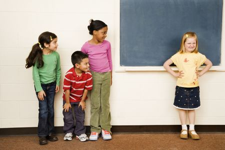 mixed race girl: Students standing in classroom. A girl is separate from the group. Horizontally framed shot. Stock Photo