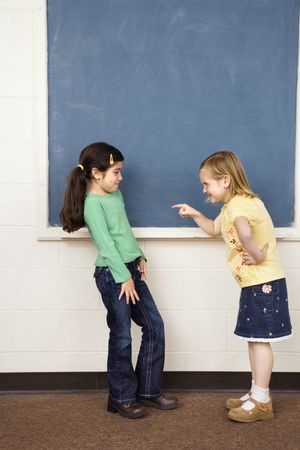 Girl pointing finger at other girl in school classroom. Vertically framed shot. photo
