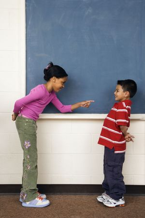 Girl pointing finger at boy in school classroom. Vertically framed shot. photo