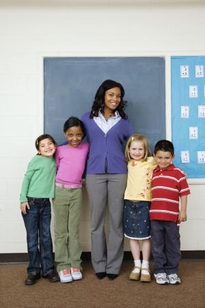 minors: Profesor posando para el retrato de grupo con los estudiantes en el aula de la escuela. Verticalmente enmarcado disparo. Foto de archivo