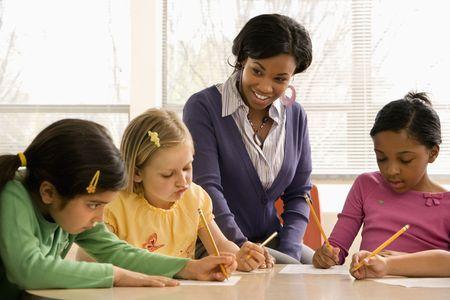 profesores: Profesor de ayudar a los estudiantes en el aula de la escuela. Disparo horizontalmente enmarcado.