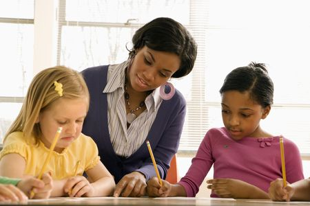 teaching: Teacher helping students with schoolwork in school classroom. Horizontally framed shot.