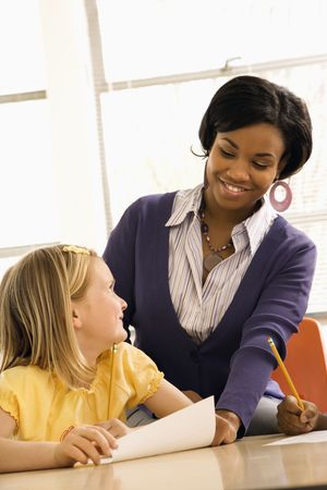 schoolwork: Teacher smiling and helping students with schoolwork in school classroom. Vertically framed shot. Stock Photo