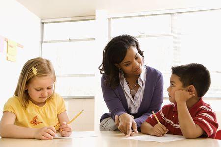 mujeres sentadas: Profesor de ayudar a los estudiantes con schoolwork en el aula de la escuela. Disparo horizontalmente enmarcado.