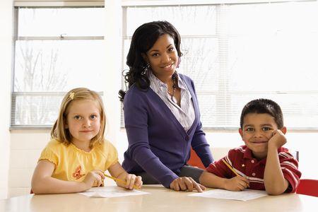 schoolwork: Teacher helping students with schoolwork in school classroom. Horizontally framed shot.