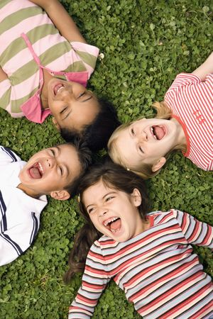 kids playground: Children lying in clover screaming and laughing with heads together. Vertically framed shot.