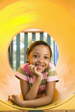 Young girl lying in yellow crawl tube at playground and smiling. photo