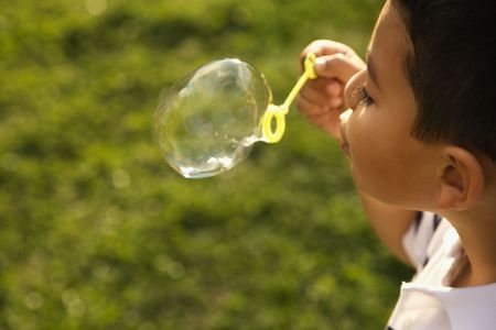 Young boy blowing bubbles outside. Horizontally framed shot. photo