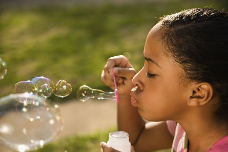 horizontally: Young girl blowing bubbles outside. Horizontally framed shot. Stock Photo