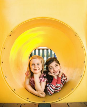 Young girls lying together in crawl tube at playground. Vertically framed shot. photo