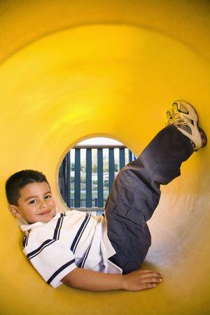 ni�os latinos: Chico joven mentir en tubo de rastreo en el patio de recreo. Verticalmente enmarcado disparo.